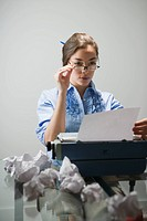 Young woman looking at document in office