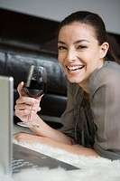 Young woman using a laptop, holding wineglass