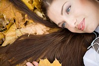 Young woman lying on autumn leaves, listening to MP3 player