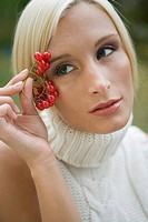 Portrait of young blonde woman holding cherry outdoors