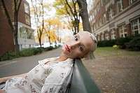 Portrait of young blonde woman leaning on bench in neighborhood