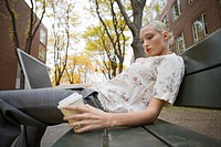 Side view of young blonde woman holding laptop and coffee cup on bench in neighborhood
