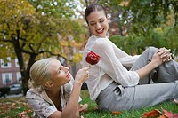 Two young women sitting in park with candy apple