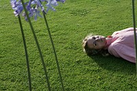 Young woman lying in park grass, high angle view.