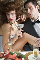 Portrait of sexy couple posing suggestively at elegant dinner party