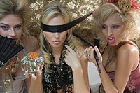 Three blonde women in lingerie playing guessing game with blindfold and exotic food