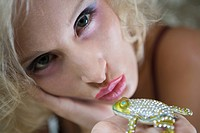 Close_up of blonde woman holding bejeweled frog