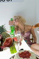 Portrait of sexy blonde woman sitting at banquet table of food with champagne bottle