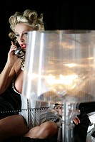 Portrait of sexy blonde woman in lingerie on the phone, lamp in foreground