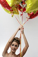 Portrait of worried young woman holding balloons, studio shot