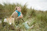 Woman on dune with hot drink