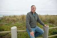 Man sitting on a fence at the coast