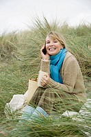 Woman on dune with mug and cellphone