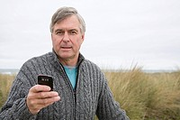 Man at the coast with smartphone