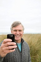 Man at the coast with camera phone