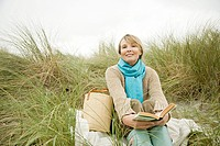 Woman with a book on a dune