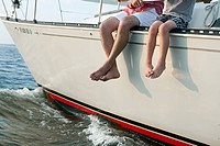 Father and son sitting on yacht, legs dangling (thumbnail)