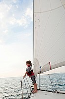 Young boy on board yacht, looking at view