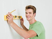 Young man using spirit level on wall