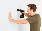 Young man using electric drill (thumbnail)