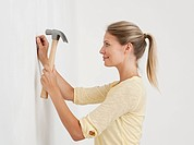 Young woman hammering nail into wall