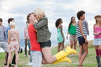 Young man lifting girlfriend and kissing her at festival
