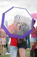 Young couple kissing behind umbrella at festival (thumbnail)