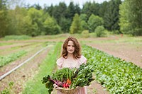 Young woman on farm with basket of vegetable produce (thumbnail)
