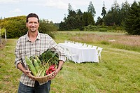 Man in field with basket of produce and table in background (thumbnail)