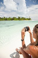 Woman taking picture, Medahutthaa Island, North Huvadhu Atoll, Maldives