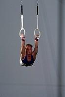 Male gymnast performing on the rings                                                                                                                  ...