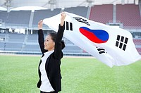 a woman holding the national flag of Korea in arena