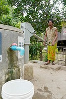 CAMBODIA. Sorn Thong Pin 55 using hand pump to get water from her well, Sesan village, Stung Treng district