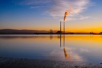 Sunset over Dublin Bay, Ireland. To the right is the iconic Poolbeg Power Station, with smoke billowing from its right cooling tower