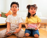 A small boy playing video game along with his sister