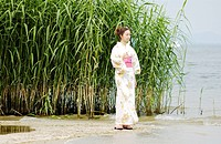 A woman in kimono standing on lake side