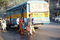 People crossing street behind blue bus , Calcutta now Kolkata , West Bengal , India