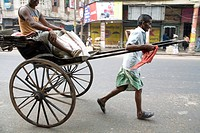 Manual labor hand rickshaw puller pulling with passenger , Calcutta now Kolkata , West Bengal , India