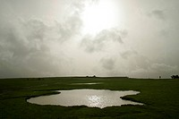 Abstract shape of pond on table land against sun setting and monsoon clouds , Panchgani , Maharashtra , India