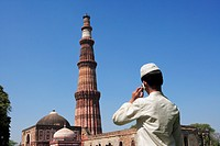 Muslim boy talking on mobile phone at Qutab Minar built in 1311 red sandstone tower, Indo_Muslim art , Delhi sultanate , Delhi , India UNESCO World He...