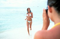 Maldives. Ari Atoll. White Sands Island. Women on beach with camera