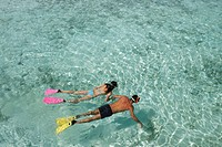 Couple snorkeling in transparent water