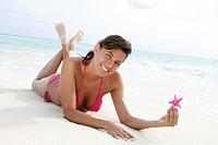 Woman´s portrait lying on beach holding a starfish
