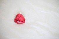 Heart shaped chocolate on pillow