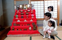 Father and two daughters looking at hinamatsuri dolls