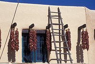 chili peppers, Taos, NM, New Mexico, Clusters of chili peppers hanging to dry outside an adobe style building in the village of Taos.