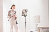 Woman holding clarinet and looking at sheet music (thumbnail)