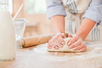 Woman kneading dough on kitchen counter