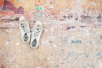 Sneakers on paint_spattered wood floor