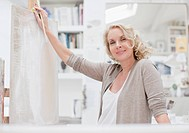 Smiling woman leaning on canvas in art studio